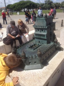 A young boy peers into the model beneath its battlements