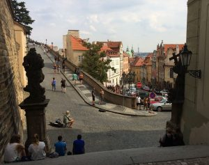 Prague street scene with people sitting on steps