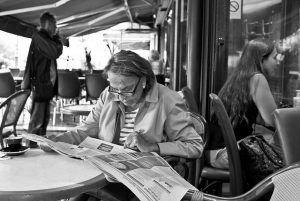 woman reading newspaper on a cafe