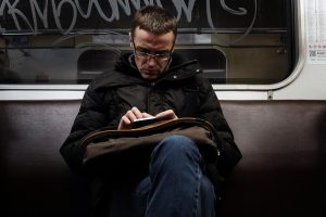 man struggling to read text on his phone