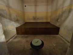 一張木床、一個馬筒,就是囚禁十幾人的囚室。