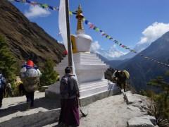 佛塔旁聚了休息的我、運貨的驢、本地人和挑夫,挑夫正把一大堆日用品運到山上。