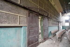 沉厚的木門上裝有半圓形用作掛上布簾的路軌,十分講究。