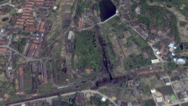 馬蹄形的路軌鋪設在矮山丘上。右邊是卸煤區和選礦廠,左邊隱約可見月台,側線盡頭是車庫。