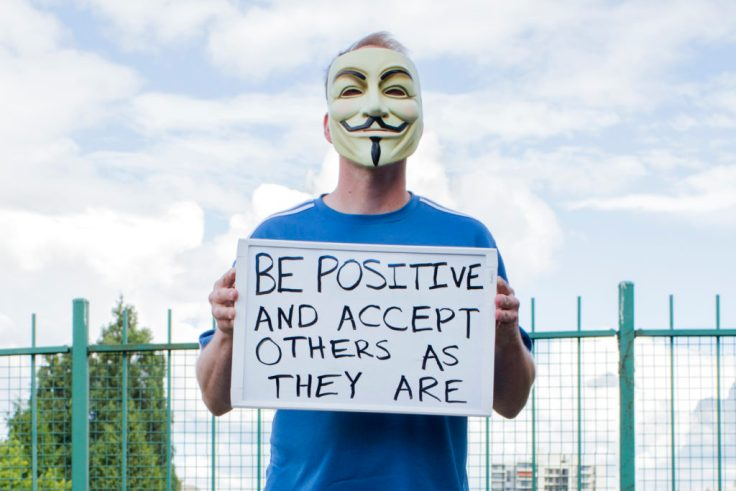 "Man in Guy Fawkes mask with a sign that reads ""Be positive. Accept others as they are."""