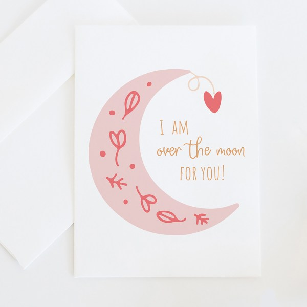 "Over The Moon || A whimsical greeting card illustrated with an illustrated moon with floral details and a whimsical hanging heart, featuring the saying ""I am over the moon for you"". >> Eight Pepperberries Paperie"