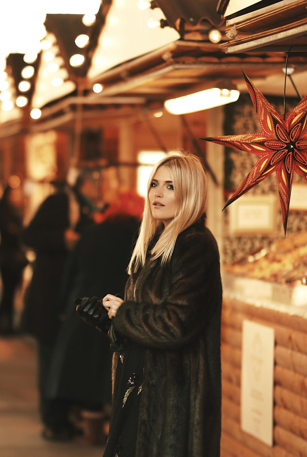 Blonde Eimear Varian Barry wearing a faux fur winter coat with a camera