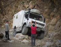 Reiseleiter und Offroad-Experte André Schwartz weist Unimog-Fahrer bei schwieriger Verschränkungspassage ein.