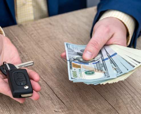 Businessman holding car key and money