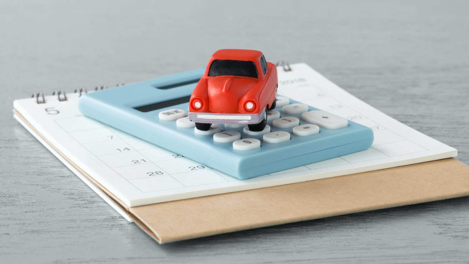 Toy car on caculator and calendar on wooden table