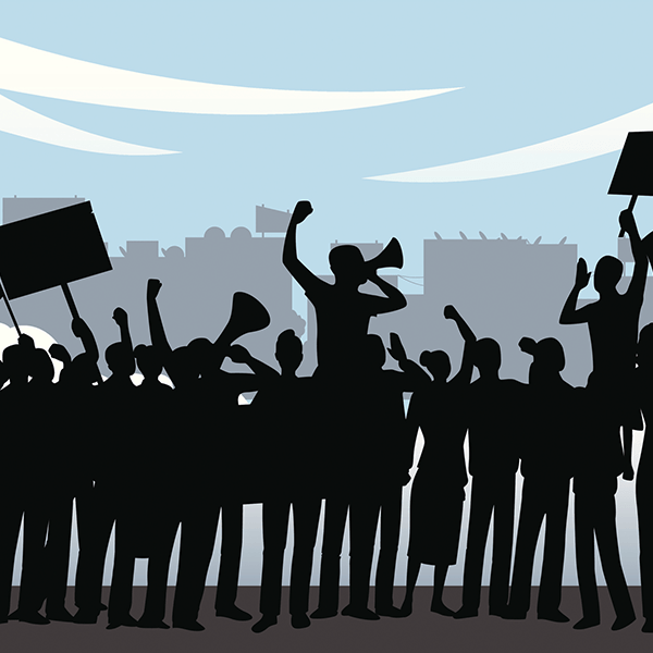 Sillouettes of protesters with signs and a megaphone