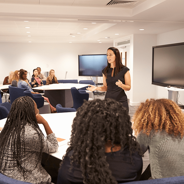 A women stands and teaches a classroom of students gathered around
