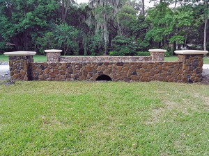Natural stone masonry - Creek rock culvert bridge and columns with cast stone column caps.