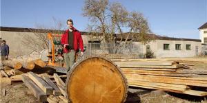 Nils Lidbaum vid sågverket från Logosol med en stor ekstock