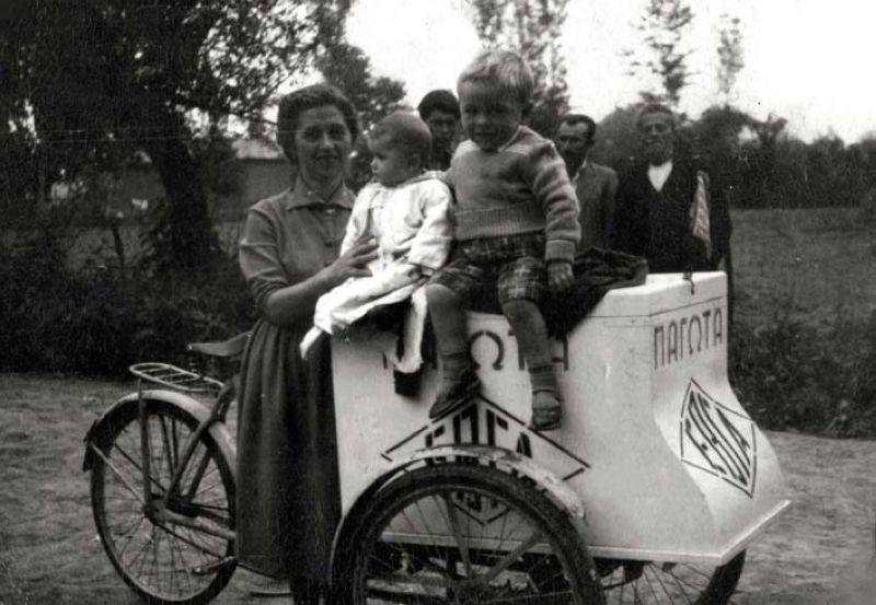 Απεικονίζεται μια γυναίκα με τα δυο παιδιά της να κάθονται πάνω στο καροτσάκι του παγωτού και από πίσω φαίνονται 3 άνδρες
