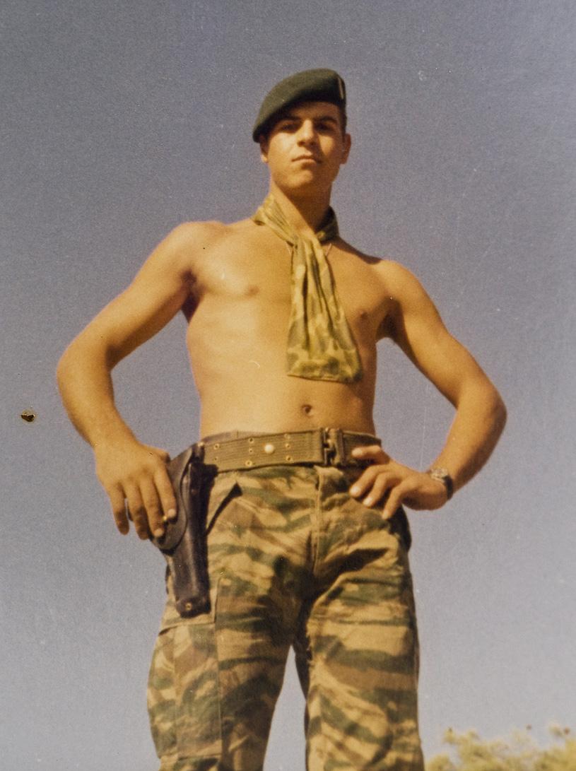 Απεικονίζεται ο Μανώλης Μπικάκης φορόντας το κάτω μέρος της στρατιωτικής στολής, με έναφουλάρι στο λαιμό, το αντίστοιχο καπελάκι του στρατού και έχει το χέρι του ακουμπισμένο στο όπλο που είναι στο ζωνάρι του