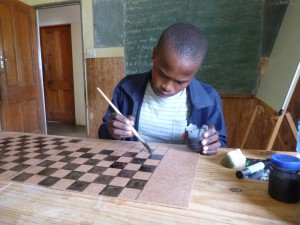 Nkosi painting a drafts board