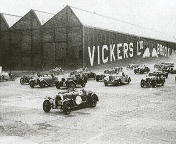 Carrera de automóviles en Brooklands con la factoría de Vickers de fondo (CC)