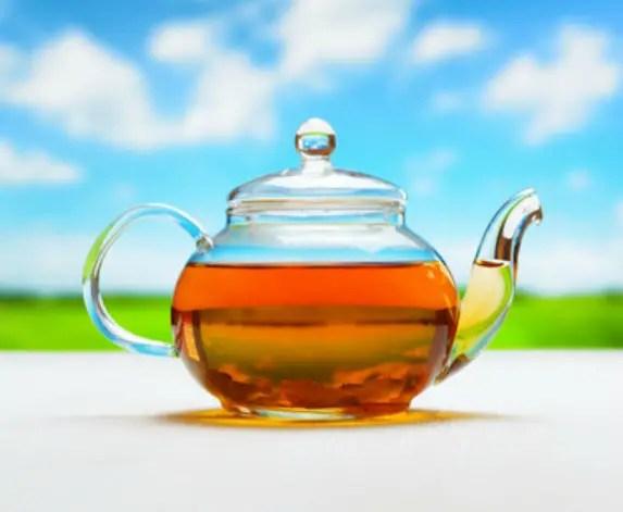 Teapot of fresh tea on natural background.