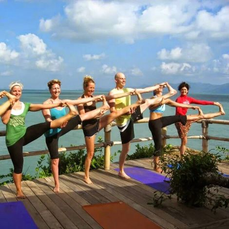 practicando yoga al borde del mar