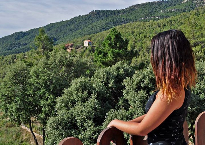 chica meditando en un retiro de yoga, rodeada de un bosque de pinos