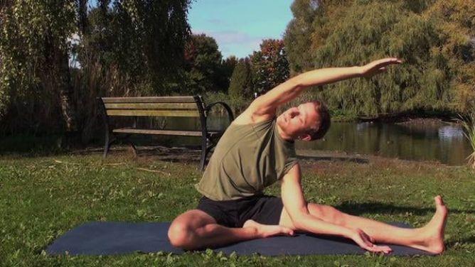 señor practicando la postura Parivrtta Janu Sirsasana en el parque