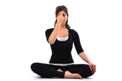 Chica sentada en loto practicando pranayama