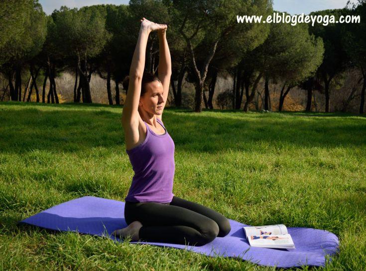 Chica realizando Virasana o postura del héroe ayudada del manual de iniciación de Yoga Iyengar