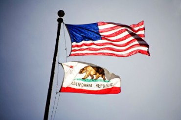 U.S. and California flags flying from the same flagpole.