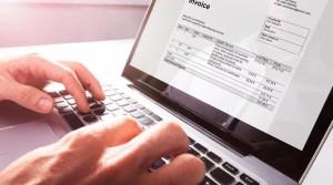 Persona generando una factura electrónica en su lap top.