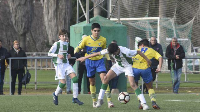 Un jugador blanquiverde protege el balón ante dos rivales del Tomares.