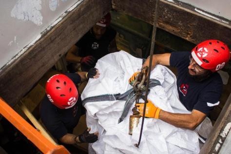 Durante la descarga, dos tripulantes del Aita Mari utilizan la grúa del barco para facilitar la descarga