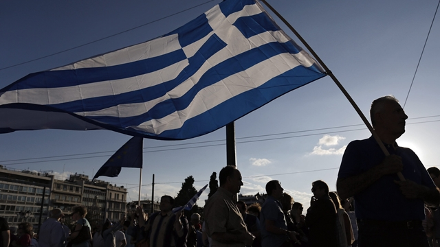 epaselect epa04814594 Protesters holds Greek flags outside the parliament during a rally demanding that Greece remains in the Eurozone, in Athens, Greece, 22 June 2015.  The Eurozone's 19 national leaders hold an emergency summit in Brussels to discuss the crisis. Fears are mounting that Greece is about to run out of money, with the country facing a 1.6-billion-euro IMF repayment deadline on June 30.  EPA/YANNIS KOLESIDIS
