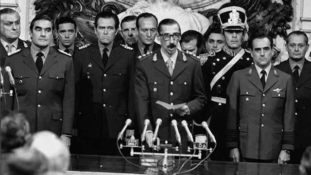 """In this file picture taken March 29, 1976, Gen. Jorge Rafael Videla is sworn in as Argentina''s new president flanked by Adm. Emilio Massera, left, and Brig. Orlando Agosti, right at Buenos Aires Government Palace after a military coup led by Gen. Jorge Rafael Videla to overthrow President Isabel Peron March 24, 1976. At least 9,000 people are officially listed as disappeared or dead during the so-called """"Dirty War"""" that right-wing military officers waged on leftists and other political dissidents after Videla''s coup. Human rights organizations put the toll of dead and missing at nearly 30,000. (AP Photo/Eduardo Di Baia) ARGENTINA ANNIVERSARY"""