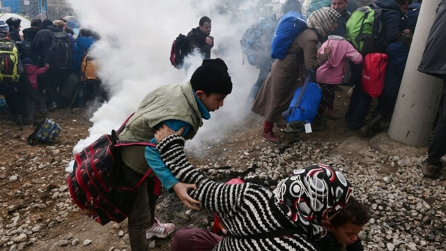 """A woman falls as refugees with their children run away after Macedonian police used tear gas to dispearse refugees trying to break the gate to enter Macedonia on February 29, 2016. Greece warned the number of refugees and migrants on its soil could more than triple next month, reaching as many as 70,000, as a Balkan cap on border crossings left thousands """"trapped"""" in the country. / AFP / LOUISA GOULIAMAKI (Photo credit should read LOUISA GOULIAMAKI/AFP/Getty Images)"""