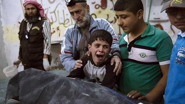 TOPSHOT - A Syrian boy is comforted as he cries next to the body of a relative who died in a reported airstrike on April 27, 2016 in the rebel-held neighbourhood of al-Soukour in the northern city of Aleppo. / AFP / KARAM AL-MASRI (Photo credit should read KARAM AL-MASRI/AFP/Getty Images)