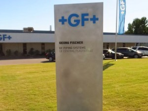 Picture of a silver monolith sign with blue logo letters.