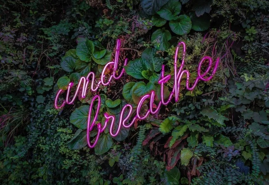 neon sign says and breathe