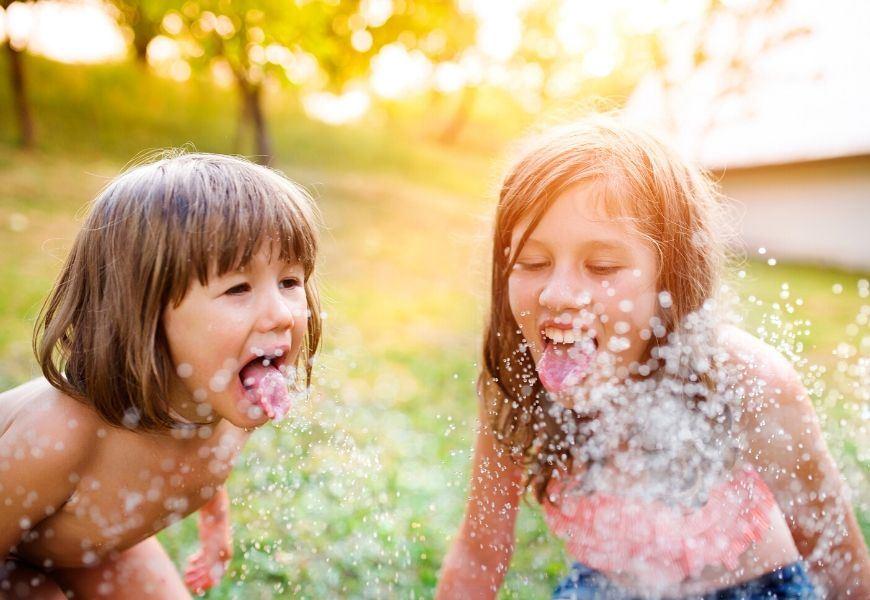 children playing in sprinkler