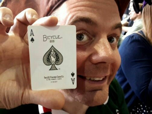 Man holding a ace of spades card.