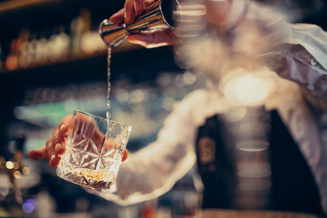 barista-bello-che-fa-bere-e-cocktail-ad-un-contatore