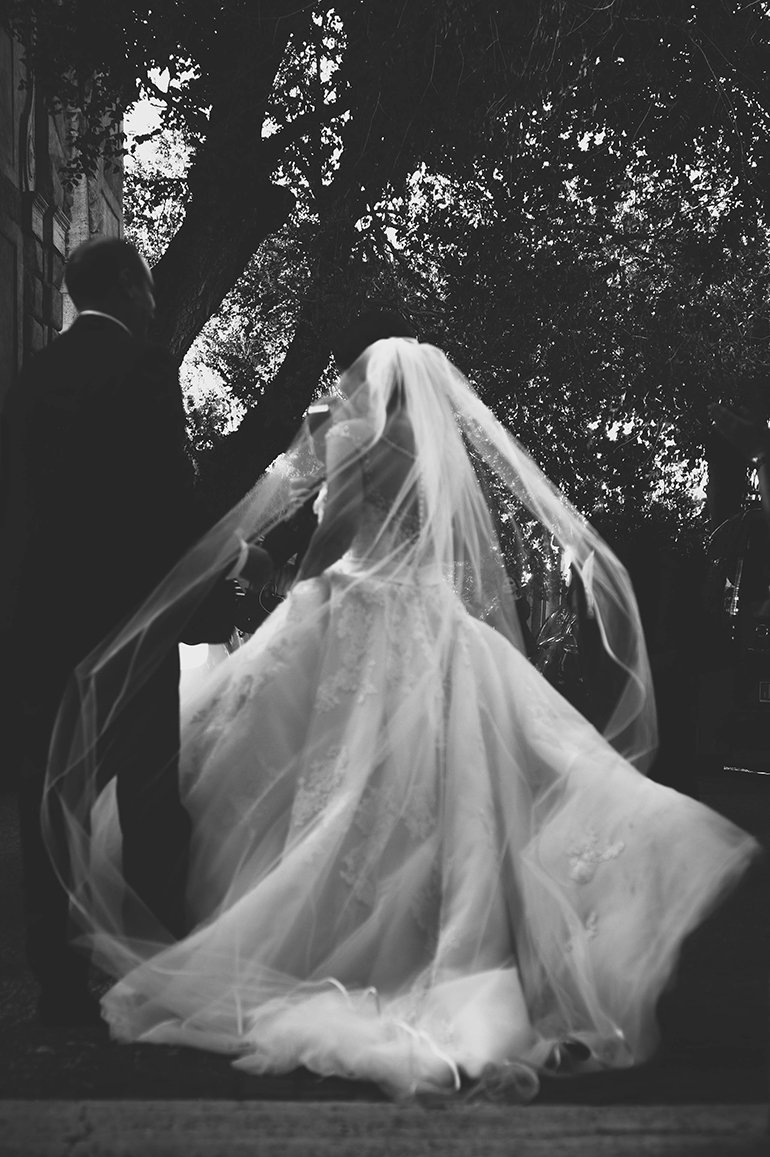 Destianation Wedding photography in Rome - exit from the church, bride dress moving for the wind