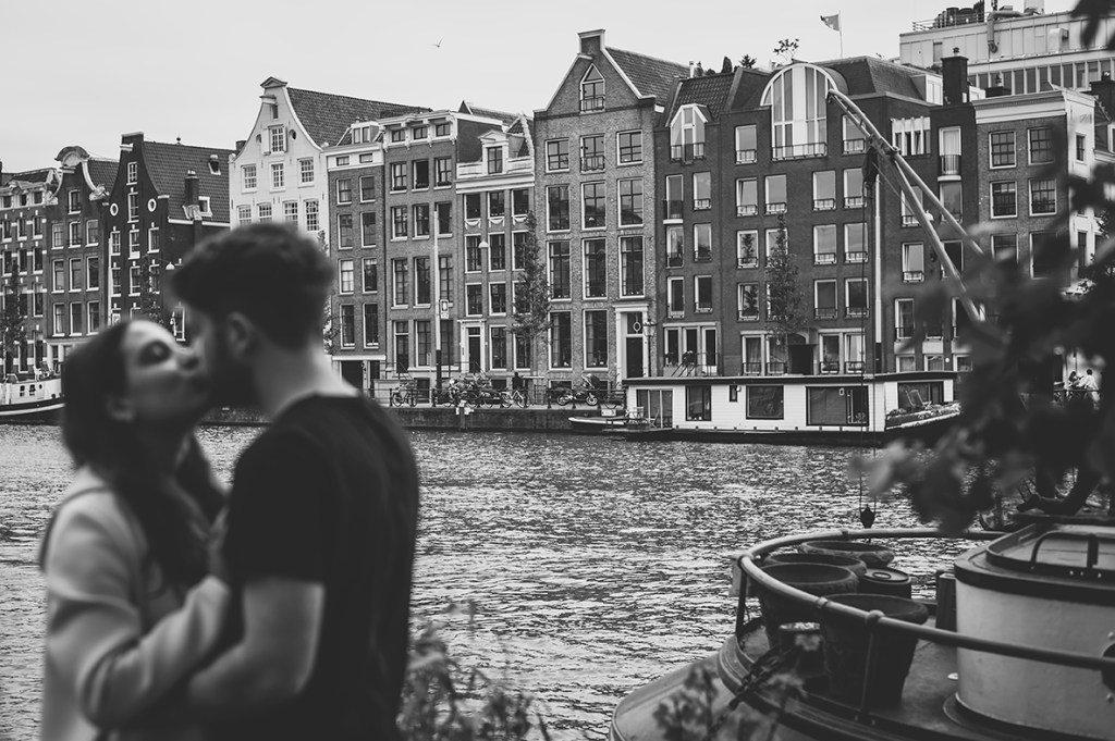 Amsterdam Couple Session - Amsterdam houses, couple in the background hugging