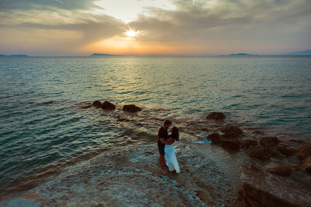 Greece Destination Engagement - Corfu - landscape at Loggas beach with couple hugging