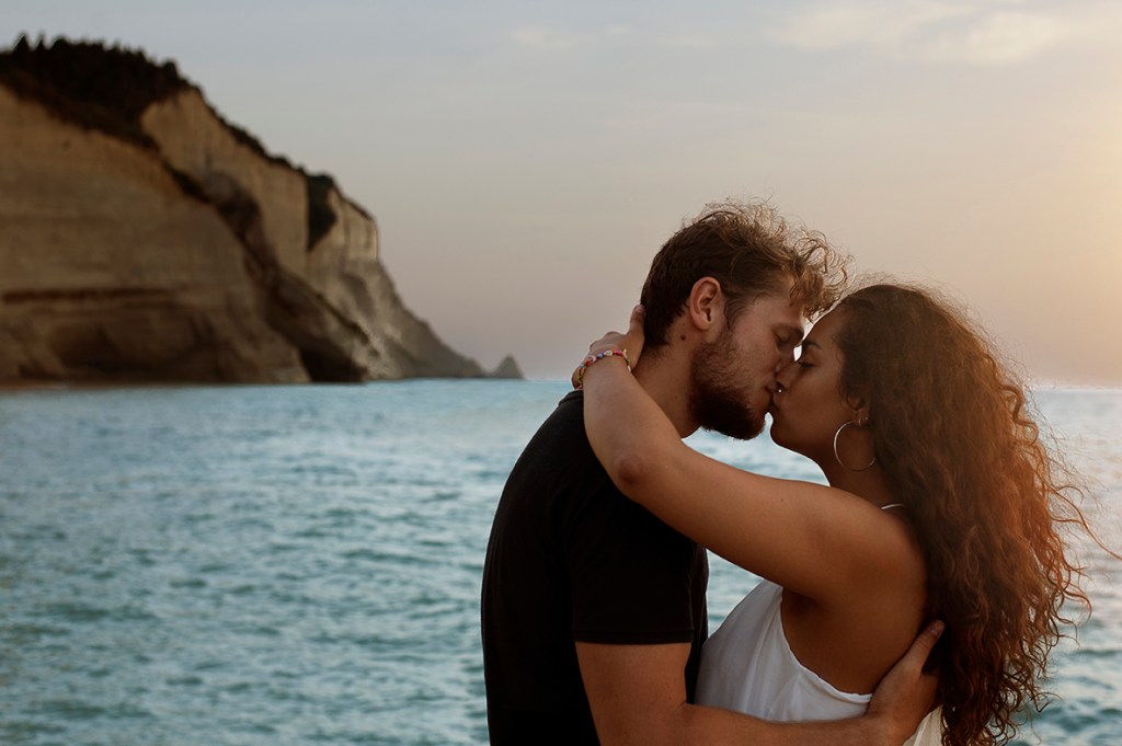 Greece Destination Engagement - Corfu - romantic kiss with blue sea background