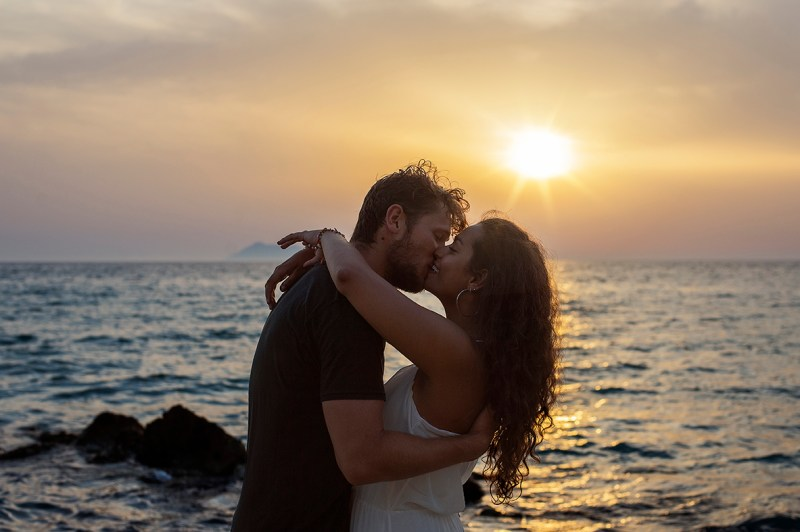 Greece Destination Engagement - Corfu - couple kissing with sunset background in Loggas Beach