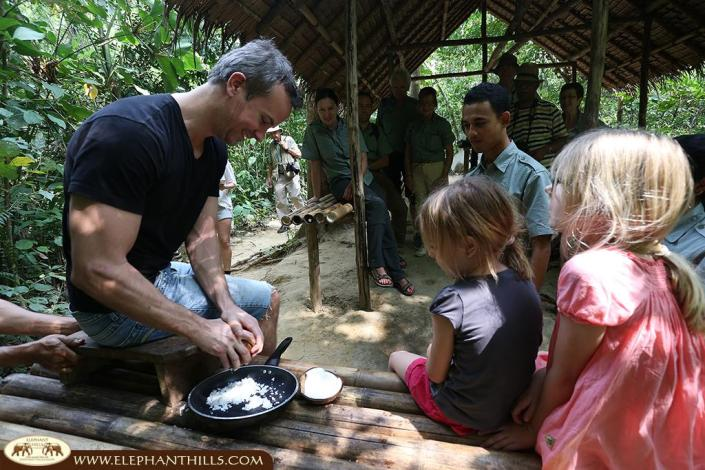 Grating fresh coconuts to prepare a fresh coconut milk for Tom Kha Gai in the Elephant Hills jungle kitchen