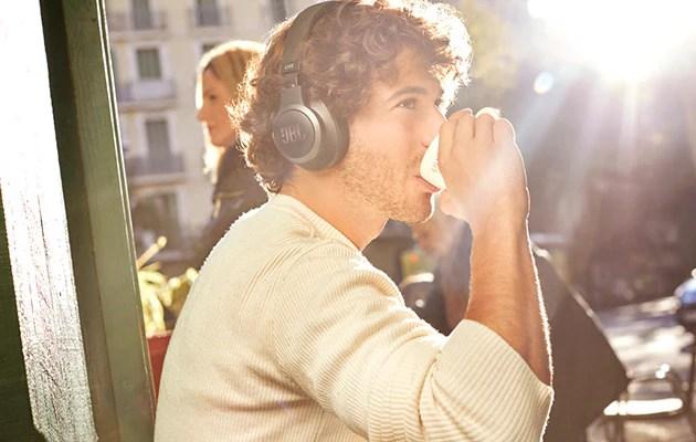 Man med svarta JBL Live-hörlurar som sitter på ett café