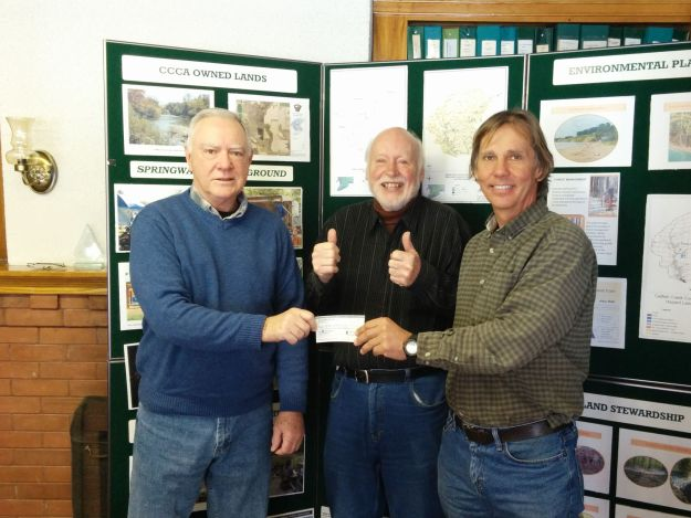 Brian King presenting cheque to Ed Pietrzak from Catfish Creek CA half of this seasons Spirit Walk proceeds as Brian Wilsdon gives a thumbs up.