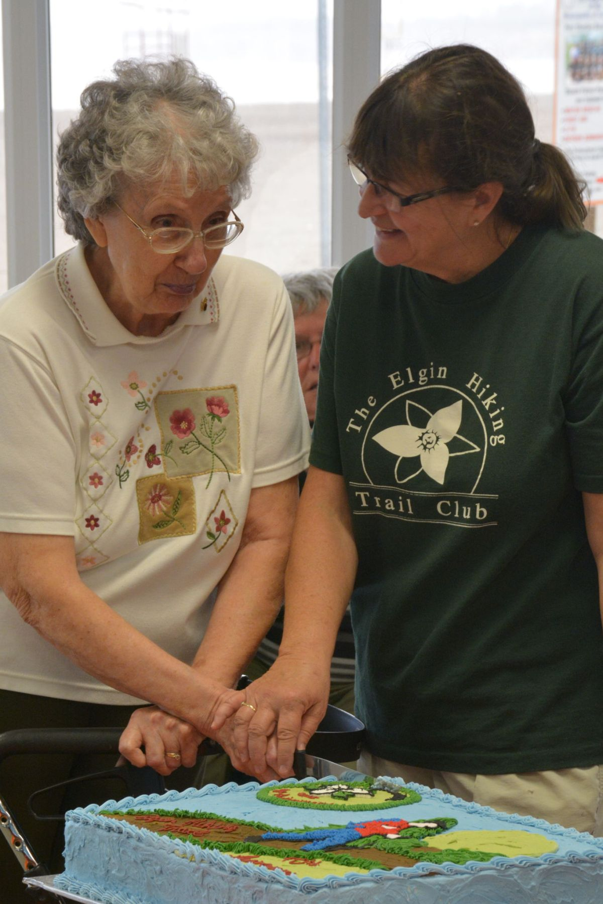 Eileene Stewart and Loretta cutting the cake which had a hiker and special 40th anniversary crest on it.